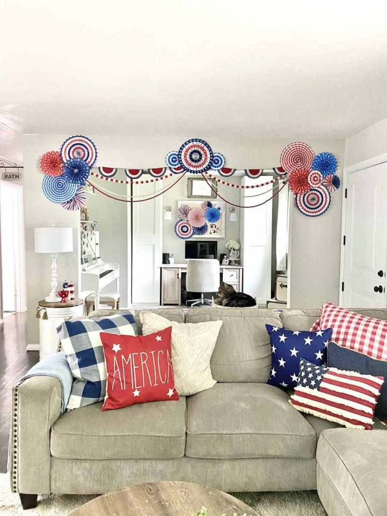 View of office with fan circle decorations, beaded garlands, and red white and blue pillows