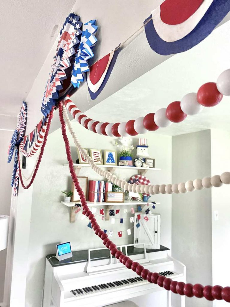 paper fan circles, banners, and red beaded garlands over office entrance